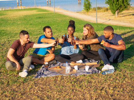 Smiling young people clinking beer bottles and eating pizza. Happy friends resting in summer park. Concept of celebration Stock Photo