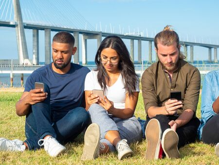 Concentrated young people using mobile phones outdoor. Young male and female multiethnic friends sitting in lawn and using smartphones in park. Technology concept