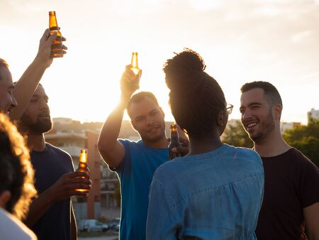Happy people cheering with beer bottles against sunset. Relaxed young friends relaxing together in park. Leisure concept 写真素材