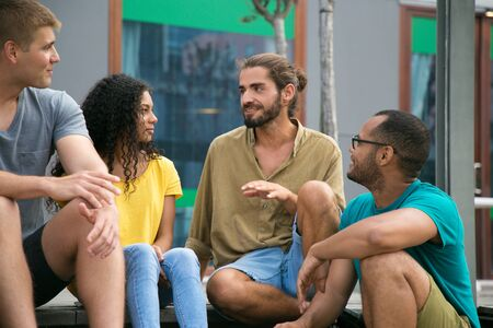 Joyful hipster guy sharing news with his friends outside. Mix raced group of young people sitting on outdoor stairs, talking, listening, laughing. Sharing news with friends concept