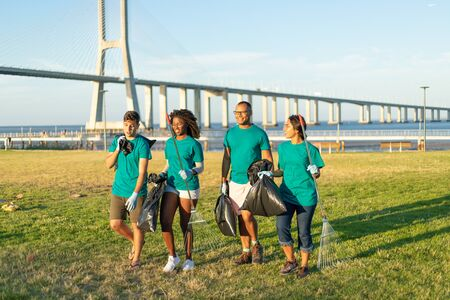 Interracial group of volunteers carrying trash from city lawn. Men and women wearing uniforms, walking on grass, holding rakes and plastic bags with litter. Garbage removal concept Zdjęcie Seryjne