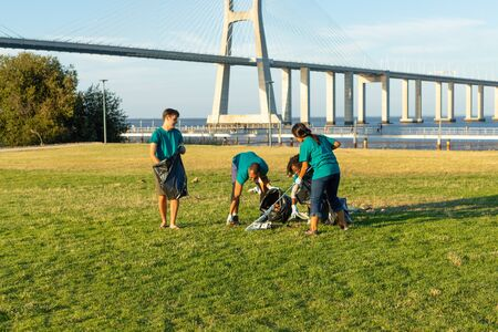 Four volunteers removing trash from grass. Men and women wearing uniforms working with rakes and picking up rubbish. Trash collection concept