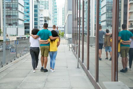 Team of male and female friends enjoying outdoor walk. Back view of mix raced people walking down city street, hugging each other and talking. Polygamy concept