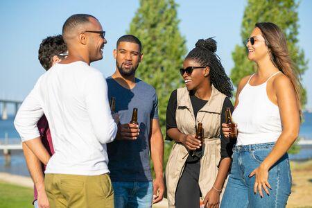 Fröhliche junge Leute mit Bierflaschen im Park. Glückliche Freunde, die auf der Wiese stehen und Bier trinken. Freizeitkonzept Standard-Bild