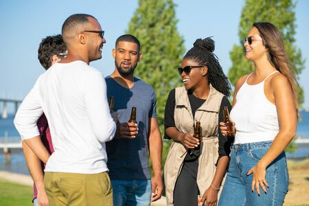 Jóvenes alegres con botellas de cerveza en el parque. Amigos felices de pie en la pradera y bebiendo cerveza. Concepto de ocio Foto de archivo