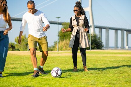 Playful friends running and kicking ball at park. Happy friends spending time together. Playing football together. Leisure concept