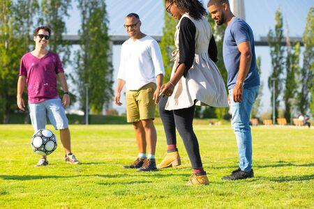 Gruppe von vier glücklichen Freunden, die Ball im Park treten. Lächelnde junge Leute, die zusammen Spaß haben. Freizeitkonzept Standard-Bild