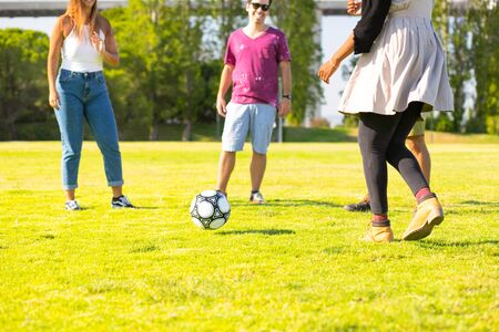 Playful friends running and kicking ball on meadow. Happy friends spending time together. Playing football together. Leisure concept