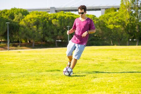 Playful young man running and kicking ball on meadow. Happy handsome guy relaxing in park. Leisure concept