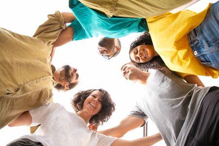 Fröhliche, fröhliche enge Freunde, die draußen umarmen und posieren. Ansicht von unten auf junge Männer und Frauen, die im Kreis stehen und sich umarmen. Hangout-Zusammen-Konzept Standard-Bild