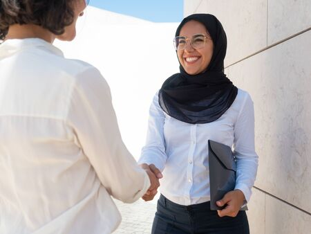Happy Muslim female professional shaking hands with colleague. Caucasian and Arab business women greeting or saying good bye to each other outside. Welcome to team concept