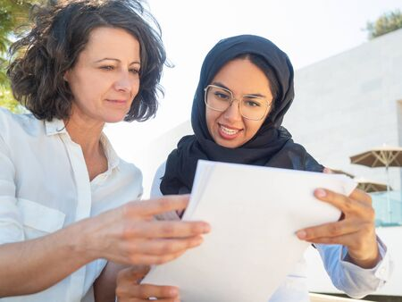 Positive focused female coworkers reviewing paper reports. Multicultural businesswomen in office clothing and Arabian veil reading and discussing document outside. Business documents concept