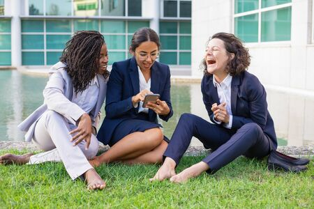 Happy barefoot businesswomen using smartphone. Cheerful multiethnic female colleagues sitting on green grass and using mobile phone. Technology concept