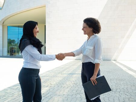 Cheerful female business partners happy to make agreement. Business women in office suits and hijab shaking hands outside and holding folder with documents. Multicultural partnership concept