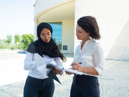 Multiethnic team of managers checking reports outside. Arab and Caucasian business women standing and reading documents. Paperwork concept