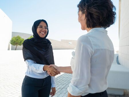 Happy multicultural business partners shaking hands. Caucasian and Arab business women discussing outdoors. Global partnership concept