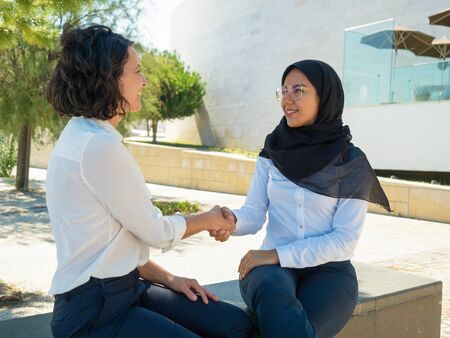 Cheerful female business partners shaking hands outside. Women in office suits and hijab discussing meeting outside and discussing cooperation. Cooperation concept