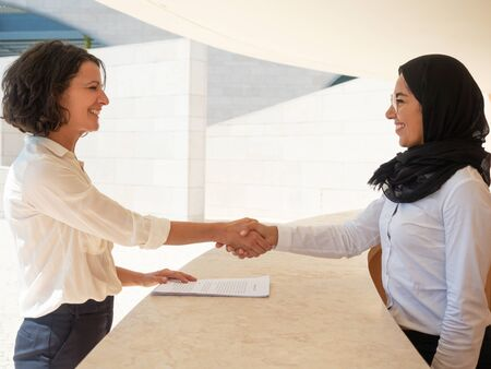 Happy Muslim hostess greeting cheerful female tourist in hotel. Caucasian and Arab women in formal suits shaking hands over reception desk. Reception desk concept