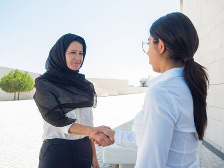 Female business partners meeting outside. Latin and Muslim business women discussing contract, shaking hands, greeting each other. Global collaboration concept