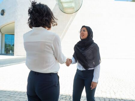 Female business colleagues greeting each other near office building. Business women in office suits and hijab shaking hands outside. Muslim businesswoman concept Stockfoto