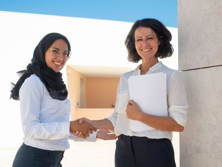 Muslim business woman shaking hands with colleague. Caucasian and Arab business colleagues greeting each other outside. Agreement or global business concept
