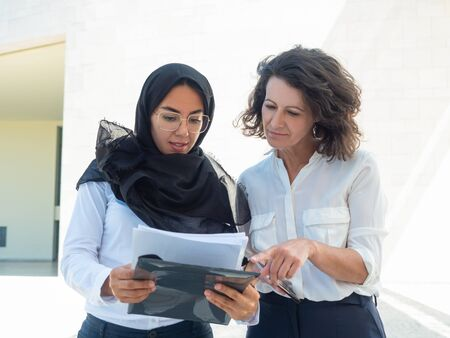 Focused female managers studying reports. Arab and Caucasian women standing and reading documents together. Paperwork concept