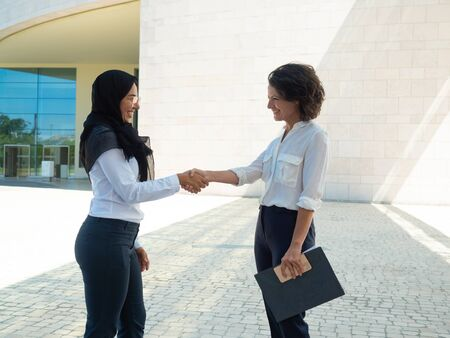 Cheerful business colleagues greeting each other outside. Caucasian businesswoman holding file and shaking hands with Muslim coworker. Multiethnic collaboration concept Stockfoto