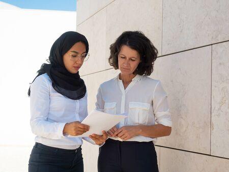 Des professionnels sérieux et concentrés vérifiant les rapports à l'extérieur. Femmes d'affaires arabes et caucasiennes debout et lisant des documents. Concept de révision de documents