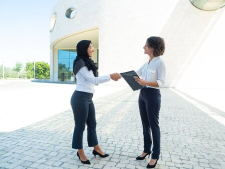Happy HR manager and candidate finishing meeting. Caucasian businesswoman holding file and shaking hands with Muslim colleague. Multiethnic company concept Stockfoto
