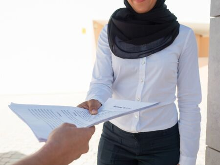 Muslim businesswoman showing documents to expert. Business woman wearing hijab giving papers to colleague. Paperwork or expertise concept