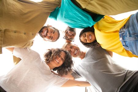Group portrait of happy close friends hugging outside. Bottom view of young men and women standing in circle and embracing each other. Friendship and unity concept