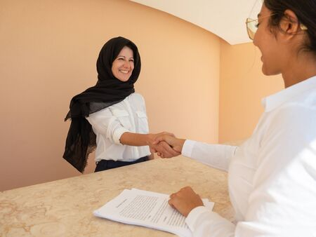 Happy business woman in hijab sealing deal. Businesswomen in formal suits shaking hands over desk with documents. Agreement concept