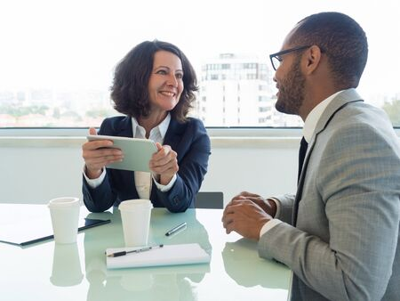 Two excited coworkers discussing team project in meeting room. Happy business woman holding tablet and talking to male colleague. Teamwork concept