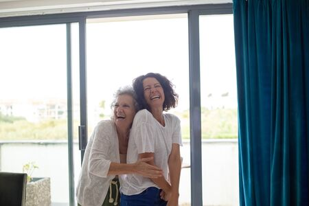 Happy mother and daughter laughing together at home. Cheerful senior mother with middle aged daughter standing together near window and laughing at home. Emotion concept Stock fotó