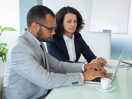 Serious professional team working on project and using laptop together. Business man and woman sitting at computer in meeting room. Teamwork concept