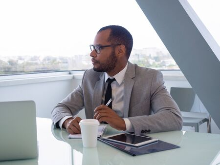 Serious young office worker listening to trainer. Business professional sitting at meeting table, looking away, speaking and writing notes. Hardworking intern concept