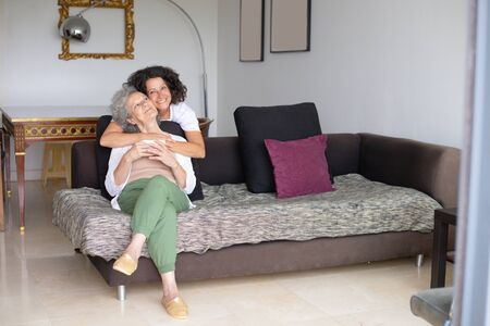 Happy mother and daughter hugging on couch. Full length view of cheerful middle aged woman with senior mother spending time together at home. Family concept