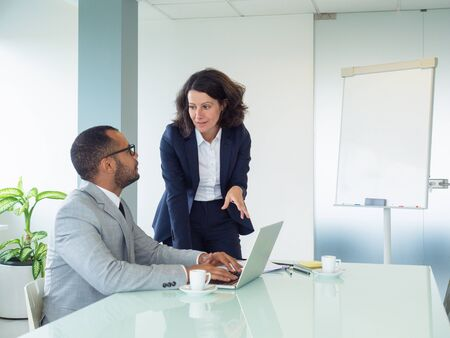 Senior female employee teaching male intern how to use corporate software. Business man sitting at laptop and listening to his colleague. Internship concept