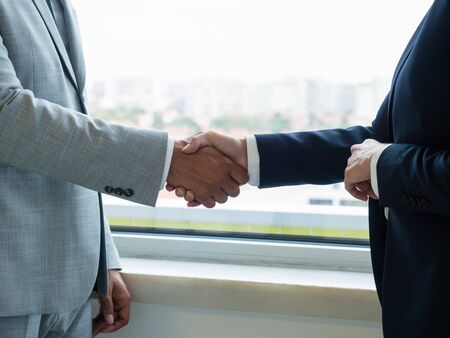 Male and female partners closing deal or agreement. Closeup os business man and woman shaking hands with each other. Contract or partnership concept Stockfoto