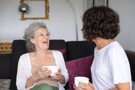 Happy mother and daughter drinking tea. Cheerful senior mother with adult daughter sitting on couch and holding cups at home. Togetherness concept Stock fotó
