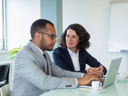 Senior employee teaching newcomer. Business man and woman using laptop together and talking in boardroom. Working on project concept Stock Photo