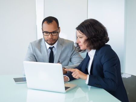Female mentor showing presentation on laptop to intern. Business man and woman sitting at computer and looking at screen, woman speaking. Mentoring concept Stock Photo