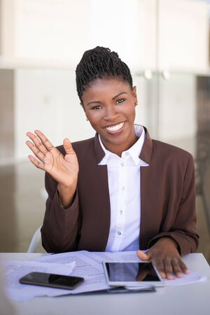 Happy young businesswoman posing for camera. Joyful African American business woman waving hello and smiling. Young businesswoman concept 스톡 콘텐츠