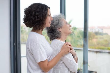 Mother and daughter looking at window. Side view of senior mother and middle aged daughter standing together and looking at window. Togetherness concept