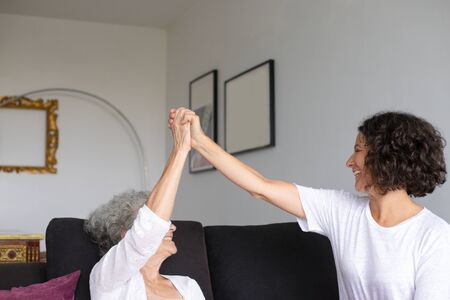 Cheerful mother and daughter giving high five. Happy senior mother and smiling middle aged daughter holding hands together at home. Relationship concept