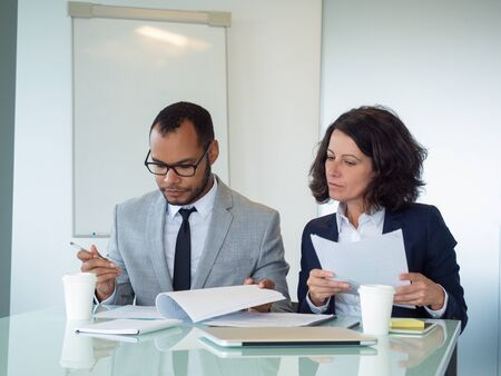 Serious legal advisors checking documents. Serious focused business man and woman sitting at meeting table and reading papers together. Legal expertise concept Stockfoto