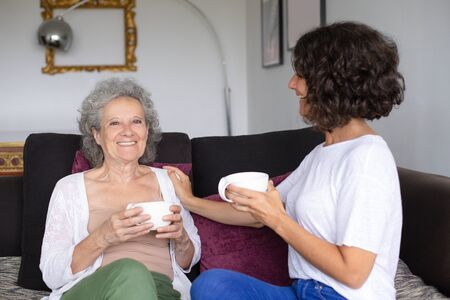 Cheerful mother and daughter drinking tea. Happy senior mother with adult daughter sitting on couch and holding cups at home. Togetherness concept