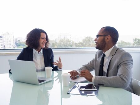 Happy female mentor explaining work issues to male intern. Business man and woman sitting at meeting table with open laptop and talking. Partnership concept Stock Photo