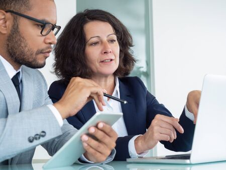 Professionals discussing and studying reports on tablet and laptop. Business man and woman sitting at office table, using computer and tablet. Teamwork concept Stock Photo