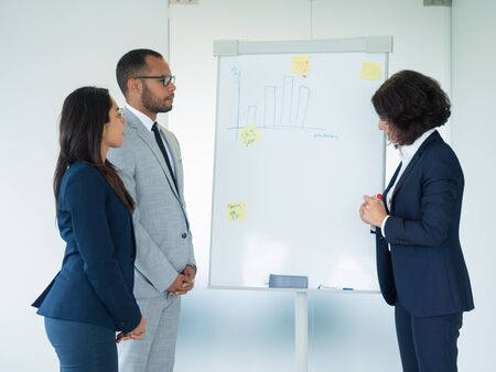 Trainer explaining statistics to interns. Business woman standing at white board with marker, her two colleagues looking at her. Training concept